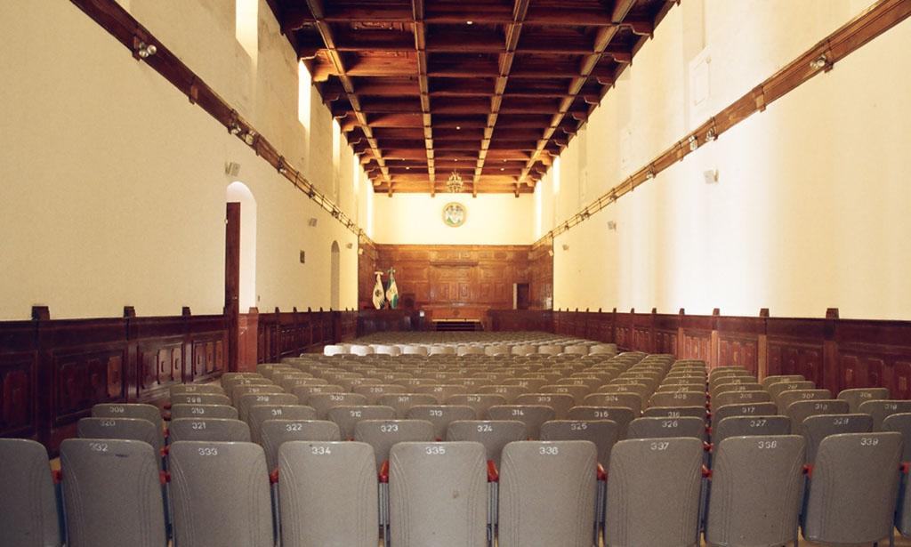 """Salón General Mayor """"Adolfo Mijangos López"""". Se observan las butacas en filas, revestimiento de madera y al fondo, el estrado con las banderas y el escudo de la USAC. Además el artesonado de madera restaurado en 1960."""