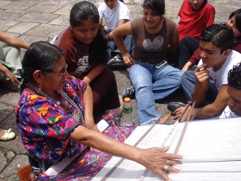 Una artesana demuestra a un grupo de estudiantes el proceso de tejido en telar maya. Se aprecia el telar, la trama y urdimbre y los colores característicos del traje regional del lugar, predomina el morado con detalles de amarillo, rojo y verde.
