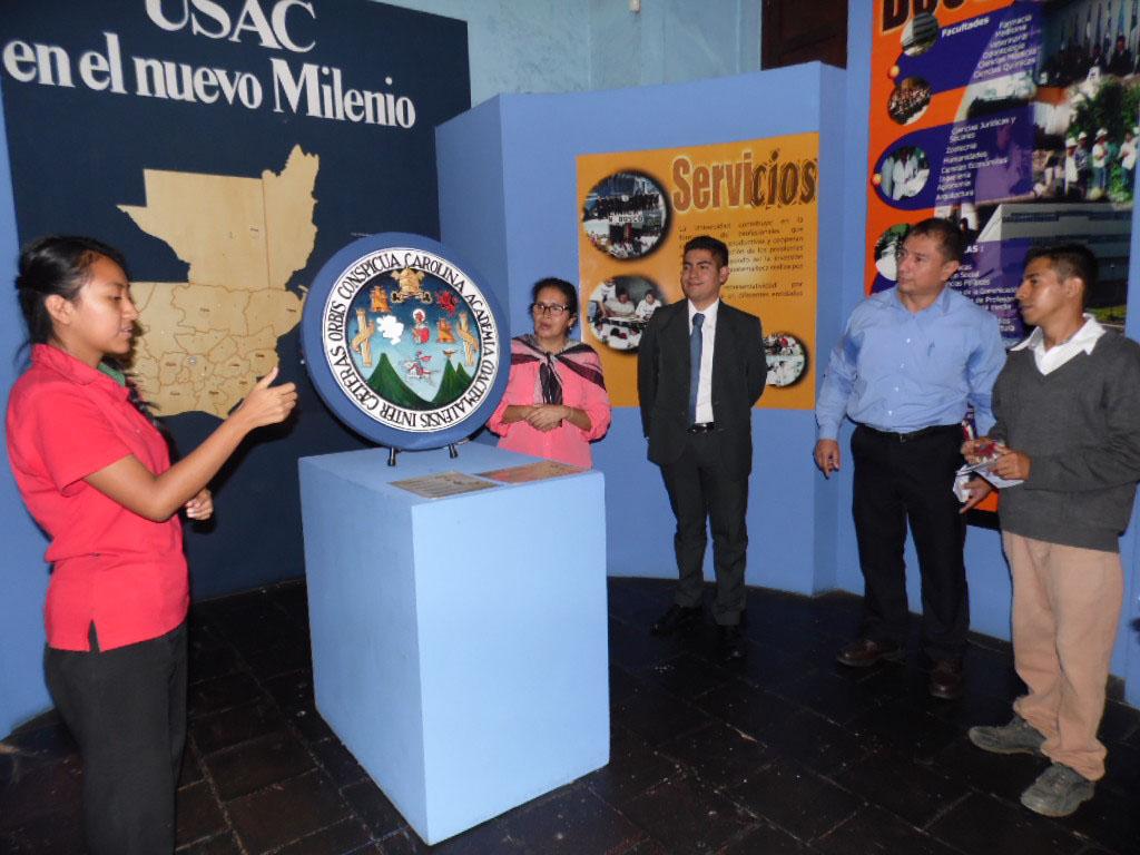 """Cuatro visitantes y una guía en el segmento de la época contemporánea de la exposición """"USAC en el Nuevo Milenio"""", la guía utiliza Lenguaje de Señas Guatemalteco. Al centro se aprecia el escudo de la USAC fabricado en madera para material didáctico, un mapa de Guatemala y carteles informativos."""