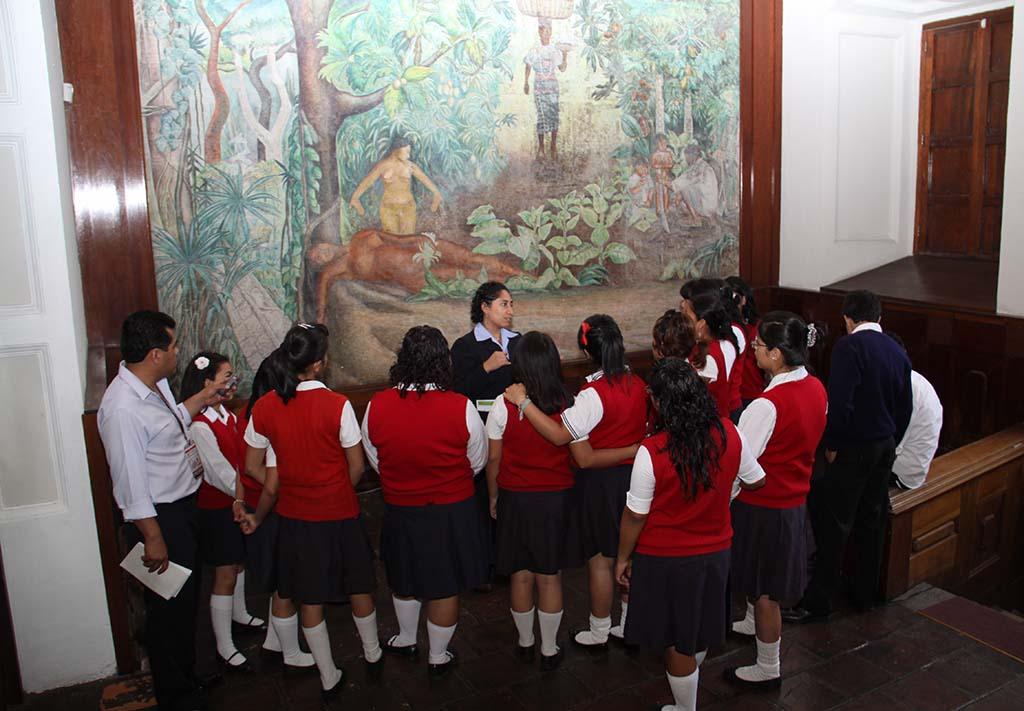 """Grupo de estudiantes uniformados, escuchan el discurso sobre el Mural """"Tierra Fértil de Guatemala"""" de la artista Rina Lazo, dirigido por guía de Museo. Al fondo se aprecia la obra mural al fresco con los elementos que la conforman vasta vegetación, mujeres que simbolizan la fertilidad, la siembra y la cosecha y una familia que labra la tierra."""