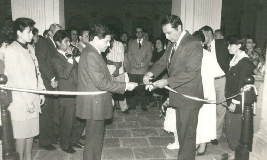 Autoridades de la USAC cortan la cinta simbólica en el acto de inauguración del Museo Universitario, se aprecia la concurrencia, todos con traje formal.