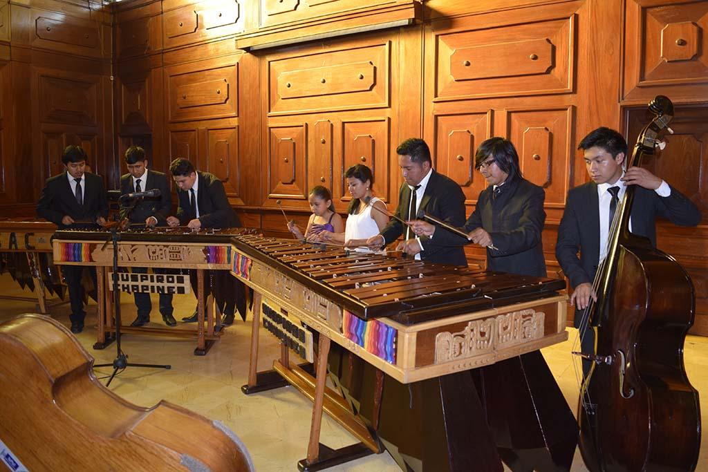 """Ocho integrantes de la Marimba """"Suspiros Chapines"""", seis jóvenes y dos niñas, interpretan el repertorio de música nacional durante el Ensamble de Marimba en el monumental e histórico, Salón General Mayor del MUSAC."""