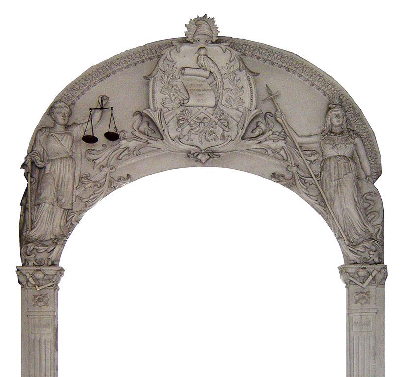 Alto relieve en yeso con dos efigies mitológicas, las musas Temis con una balanza en su mano y Palas con una lanza, sobre columnas jónicas y el escudo nacional en medio coronado con un gorro frigio.