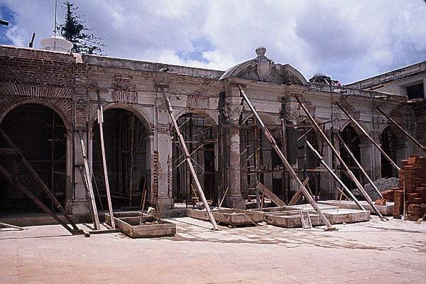 La arcada norte del antiguo Edificio de la Universidad en proceso de restauración, apuntalada con madera para evitar el desplome a raíz del terremoto de 1976. Se aprecian ladrillos y estructuras de madera en el piso del patio central.