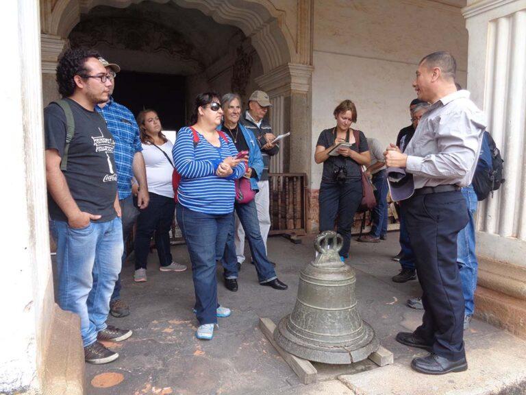 Los participantes escuchan al historiador, se observa la Casa de Alcántara, segunda sede de la Universidad.