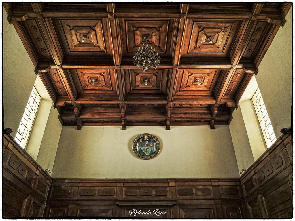 """Artesonado de madera del Salón General Mayor """"Adolfo Mijangos López"""", cubriendo el techo y zócalo del salón, adornado con una lámpara de cristal colgante y el escudo de la USAC al fondo."""