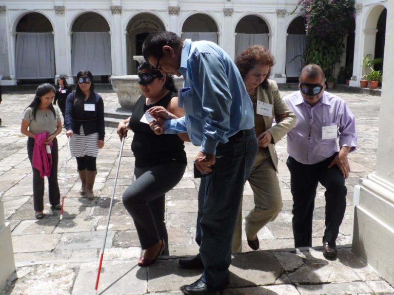 Talleristas intentan caminar con los ojos cubiertos por el claustro del MUSAC, dirigidos por personas con los ojos descubiertos, para experimentar la discapacidad visual.