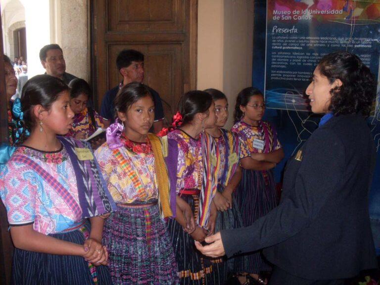 Visitas guiadas dirigidas a diferentes públicos. Al frente se aprecian niñas de Quetzaltenango con su traje maya escuchando el discurso del MUSAC.