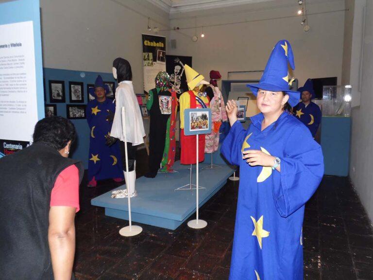 """Voluntarios de la Comparsa de la Mascarada Huelguera con trajes coloridos atienden a los visitantes en la Exposición """"Centenaria Huelga de Dolores""""."""